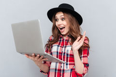 Portrait of a happy girl in plaid shirt holding laptop. Portrait of a happy pretty girl in plaid shirt holding laptop and waving while having video conversation Stock Photo