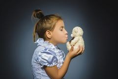 Portrait of happy girl playing with teddy bear isolated on gray stock photos