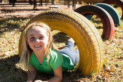 Portrait of happy girl playing with tire. At playground Stock Images
