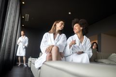 Portrait of happy cheerful girl in robe talking with her friend royalty free stock image