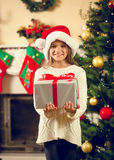 Portrait of happy girl in santa cap posing with Christmas gift b Royalty Free Stock Image
