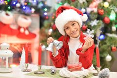 Girl preparing for  Christmas. Portrait of happy girl in Santa hat preparing for  Christmas sitting at the table Stock Photos
