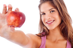 Portrait of happy girl showing red apple. In isolated white background stock photo