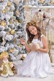 Girl near Christmas tree. Portrait of happy girl  sitting near Christmas tree with gift Royalty Free Stock Photography