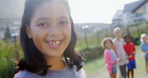 Portrait of happy girl standing in backyard 4k. Portrait of happy girl standing in backyard while her friends standing in background 4k stock footage