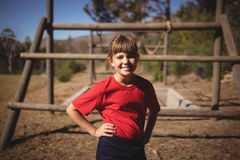 Portrait of happy girl standing with hands on hip during obstacle course. In boot camp royalty free stock image