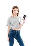 Portrait of a happy girl standing and holding mobile phone Royalty Free Stock Image