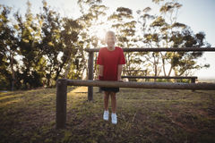 Portrait of happy girl standing near obstacle. In boot camp stock photography