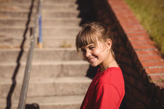Portrait of happy girl standing near staircase during obstacle course. In boot camp stock images