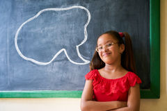 Portrait Of Happy Girl Student With Cloud On Blackboard. Concept on blackboard at school. Happy and funny latina girl in class, leaning on blackboard. Portrait royalty free stock images