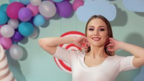 Portrait of beautiful girl near candy and balloons. Portrait of a happy girl in the Studio on a colorful background, she throws her hair posing on camera. Candy stock footage