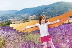 Happy girl flying like a bird with cardboard wings. Portrait of happy girl wearing costume of a bird playing in lavender field in summer Royalty Free Stock Photography