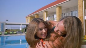 Portrait of happy girlfriends, emotional embrace of beautiful best friends near blue pool during the summer holidays at. Portrait of happy girlfriends, emotional stock video footage
