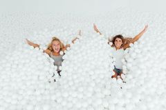 Portrait Happy Girlfriends stand surrounded by white plastic balls in the dry pool. Spend fun time. Adult childhood at Playground with pit-ball. Falling on the Royalty Free Stock Images