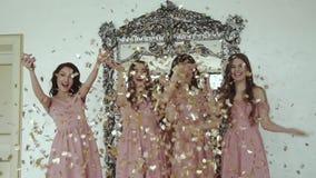 Portrait of happy girls in evening dress throwing up golden wrappers indoors stock video