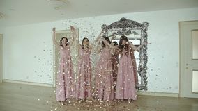 Portrait of happy girls in evening dress throwing up golden wrappers indoors stock footage