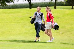 Portrait of happy golfing couple. With golf bag on green field royalty free stock photo