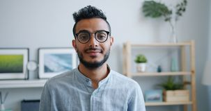 Portrait of happy good-looking Arabian guy smiling and looking at camera at home stock footage