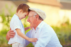 Portrait of happy grandfather and grandson bow their heads. The portrait of happy grandfather and grandson bow their heads royalty free stock photo
