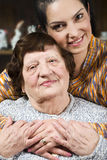 Portrait of happy grandma with her granddaughter. Portrait of a happy grandma and granddaughter sitting in a hug with  their hands together in living room,check Stock Image