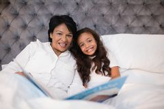 Portrait of happy grandmother and granddaughter reading book on bed Royalty Free Stock Image