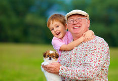 Portrait of happy grandpa, grandson and puppy Stock Image
