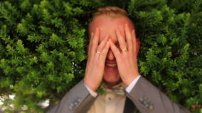 Portrait of happy groom with eyes closed on green background stock video