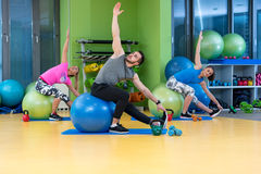 Portrait of happy group exercising on Swiss ball Royalty Free Stock Image