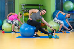 Portrait of happy group exercising on Swiss ball Stock Photo