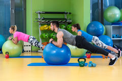 Portrait of happy group exercising on Swiss ball Stock Images