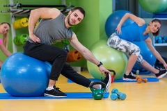 Portrait of happy group exercising on Swiss ball Stock Image
