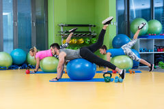 Portrait of happy group exercising on Swiss ball Royalty Free Stock Photo