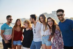 Happy group of friends standing together in row outside stock image