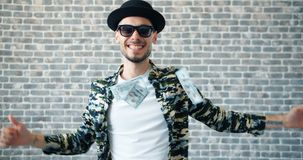 Portrait of happy guy dancing in hat and sunglasses while cash flying around