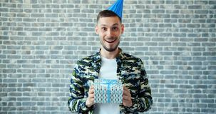 Portrait of happy guy in party hat holding birthday present shaking gift box. Looking at camera with happiness and joy then leaving. Presents and people concept stock video