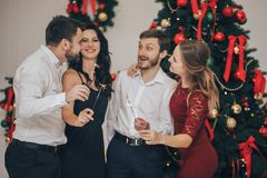 Portrait of happy guys and girls enjoying New Year party with Bengal lights. Happy guys and girls enjoying New Year party with Bengal lights stock image