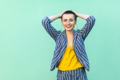 Portrait of happy handsome beautiful short hair young woman in casual striped suit standing, holding her head, looking at camera, stock photography