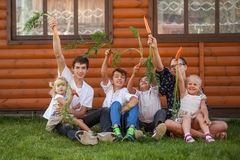 Portrait of happy handsome boys and little girl on background of wooden house Stock Photo