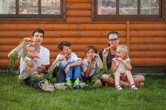 Portrait of happy handsome boys and little girl on background of wooden house Stock Images
