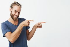 Portrait of happy handsome guy with beard joyfully smiling and pointing aside with index fingers on both hands . Copy. Space royalty free stock images