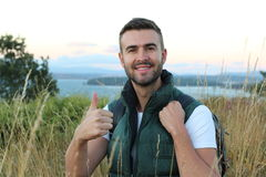 Portrait of a happy handsome man with backpack hiking into the forest with stunning view from a top of a mountain royalty free stock photography