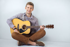 Portrait of happy handsome man playing guitar. Siting on floor Stock Image