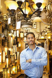 Portrait of happy handsome man standing with arms crossed in store Royalty Free Stock Photo