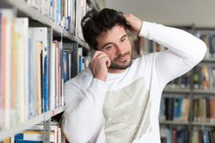 Student Talking on the Phone in Library. Portrait of a Happy Handsome Man Talking on Mobile Phone in Library at the University Royalty Free Stock Photos