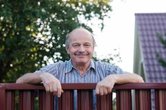 Portrait of a happy handsome mature man standing leaning on the red metal fence royalty free stock photos