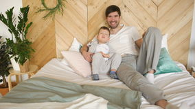 Portrait of happy handsome young father and his son lying on bed smiling and posing into camera stock footage