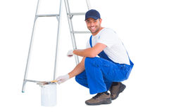 Portrait of happy handyman crouching by paint can. Full length portrait of happy handyman crouching by paint can on white background Royalty Free Stock Images