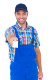 Portrait of happy handyman giving visiting card Stock Image