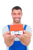 Portrait of happy handyman holding house model Royalty Free Stock Image