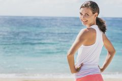 Happy healthy woman doing warm up at the beach stock image